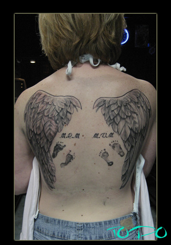 cross tattoos with wings on arm. angel wings tattoos on arm