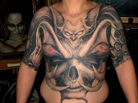 Bat face with horned skulll chest and stomach tattoo