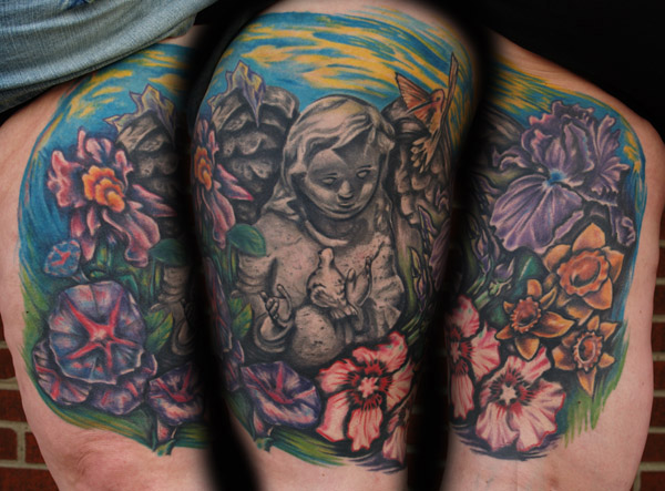 Statue and flowers memorial. Placement: Leg Comments: This is a tattoo to remember her mother. She wanted a black and gray statue with colorful flowers from