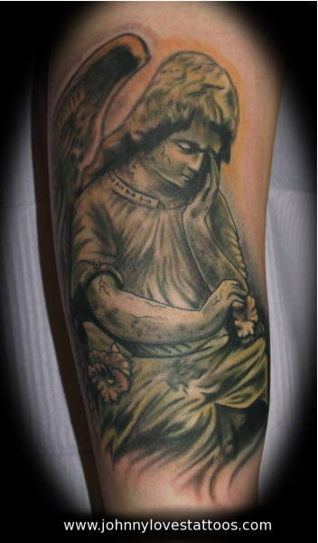Comments: an angel statue tattoo done in black and gray with green zombie