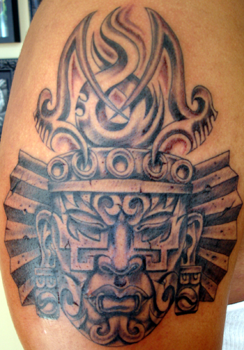 Tattoo of an aztec face on the arm